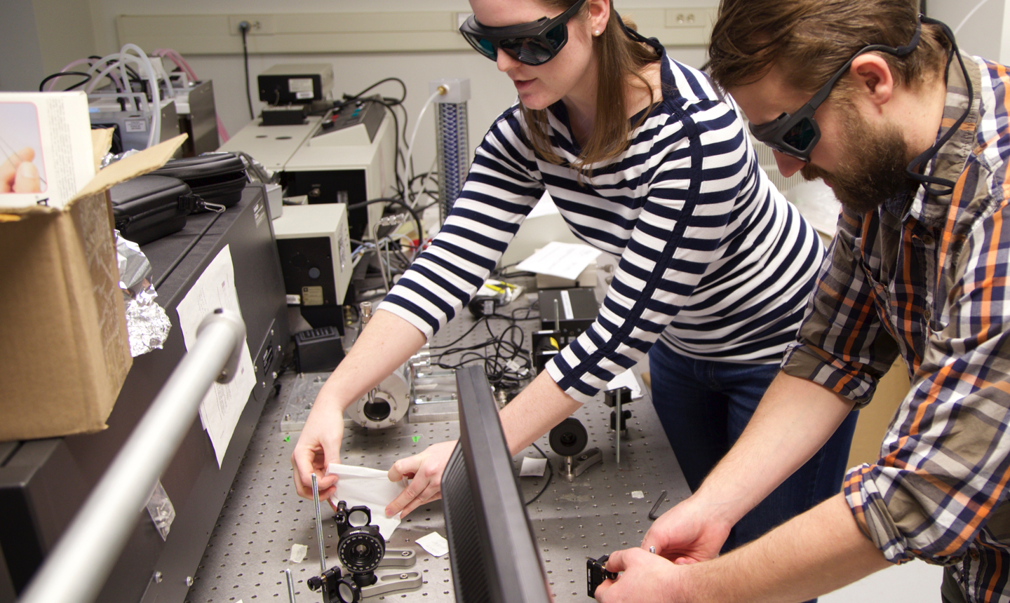 Male and female students wearing protective eyewear setting up a Chemisty experiment at a bench