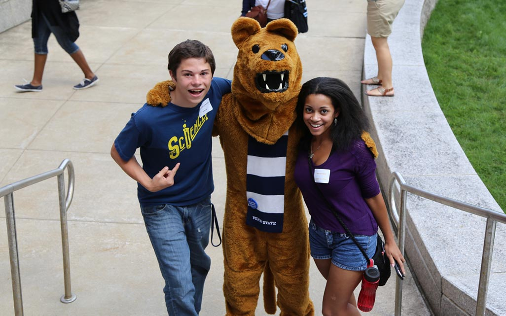 Two students pose for a photo with the Nittany Lion