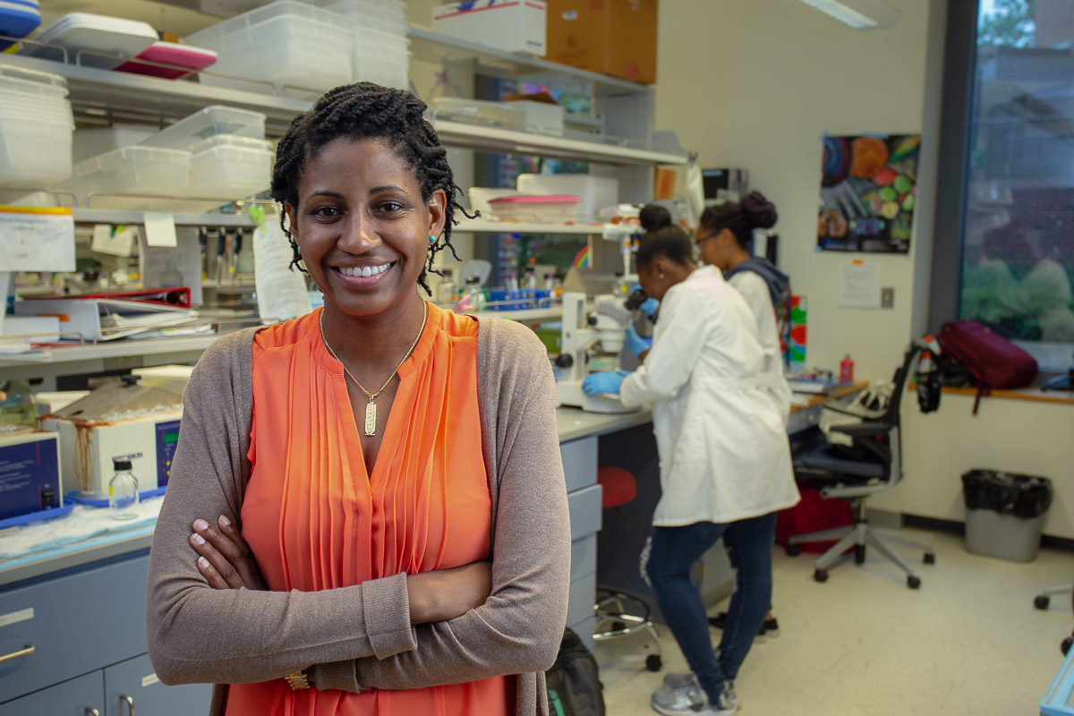 Kristin Finch posing for a headshot with a lab behind her