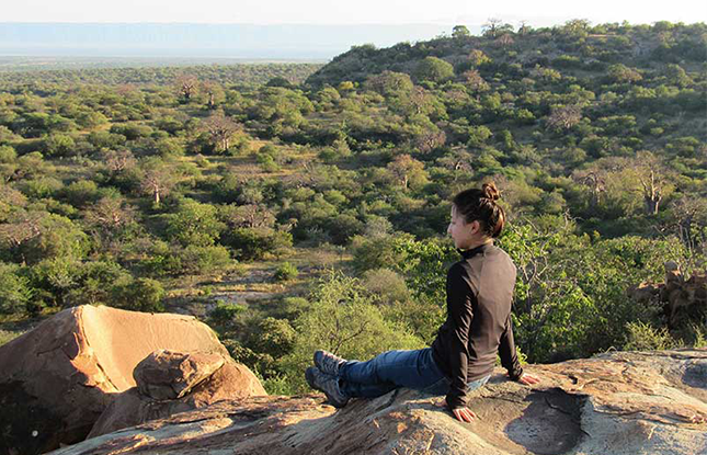 Student overlooking plains in Africa.