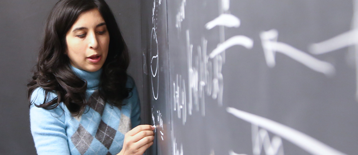 A graduate student for Mathematics writing an equation on a chalk board.