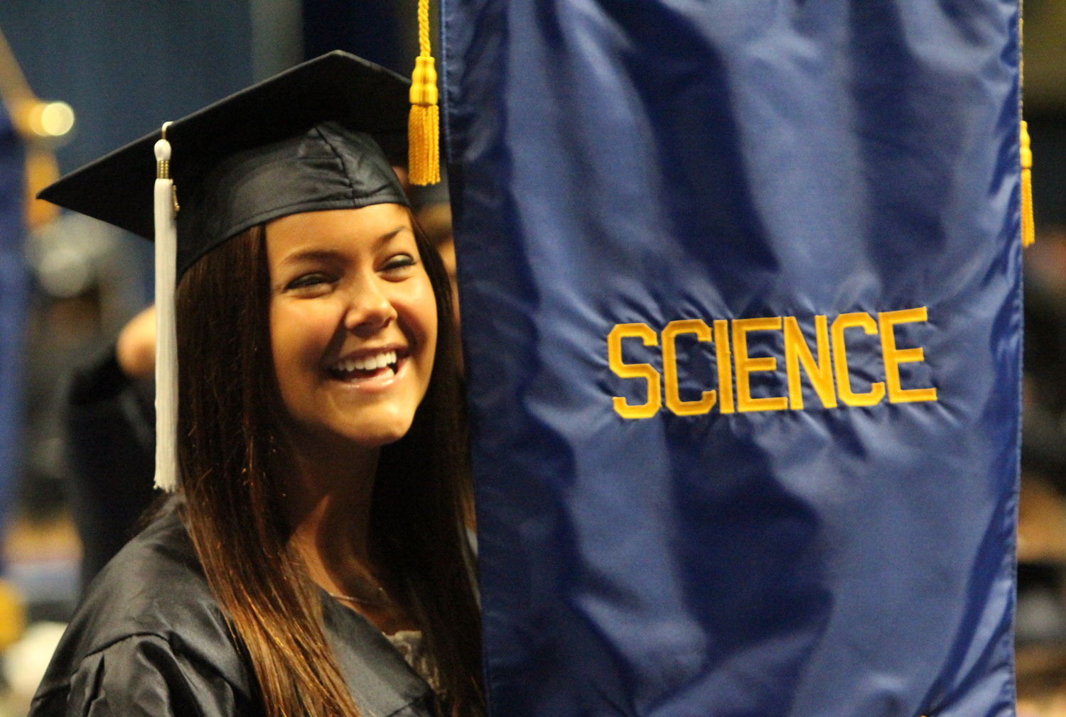 "A science major graduate standing with the ""science"" banner"