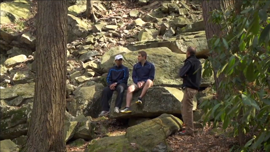 Three students sitting on rocks in the woods