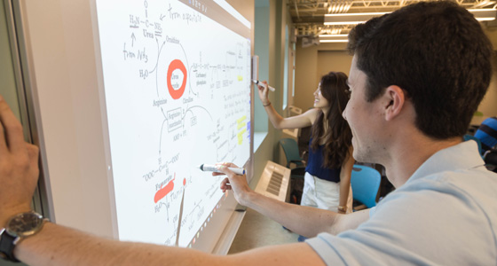 Two undergraduate students using a whiteboard in one of the study spaces available for students.