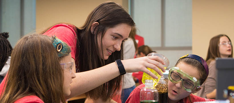 ENVISION mentor showing students a beaker of colorful chemicals