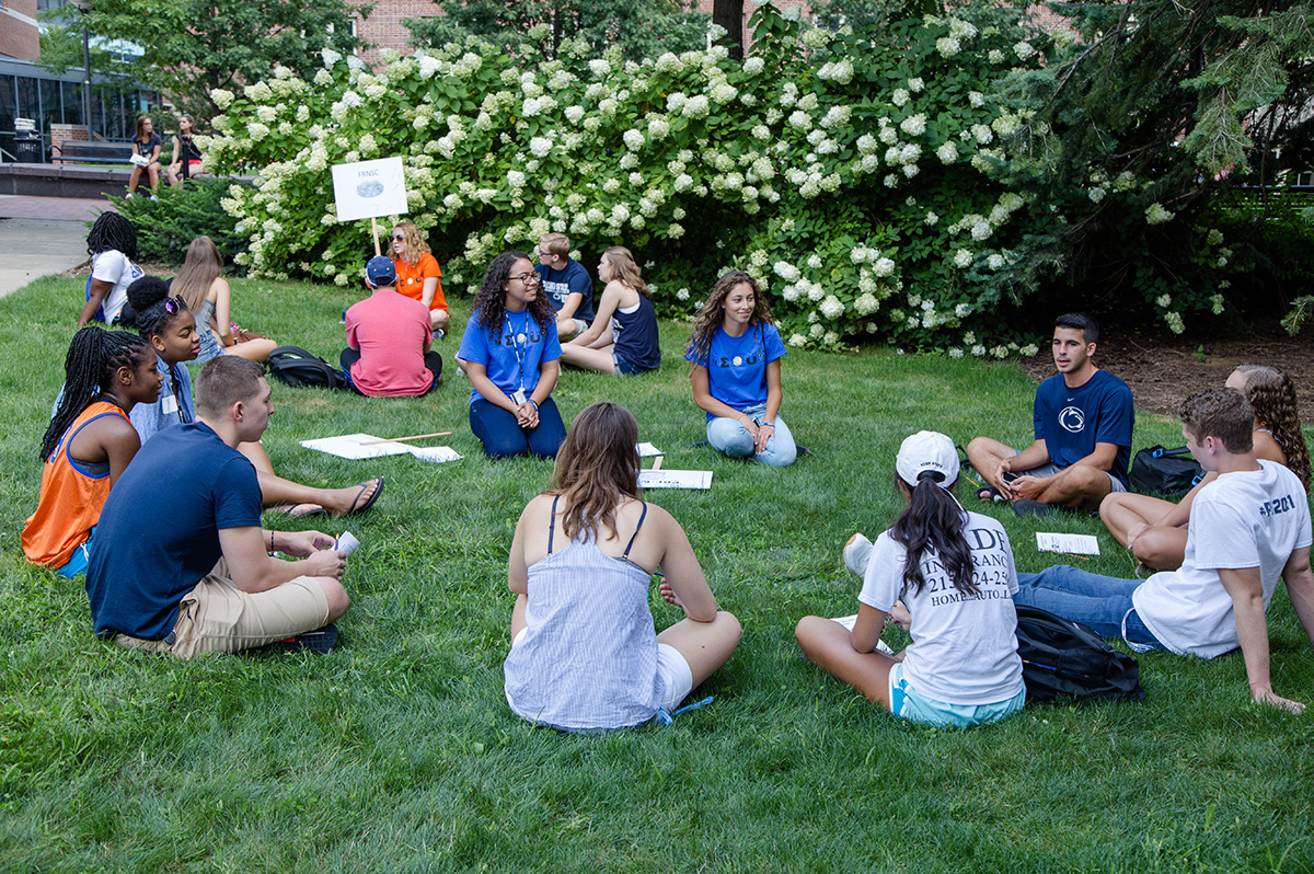 group of students sitting around in grass