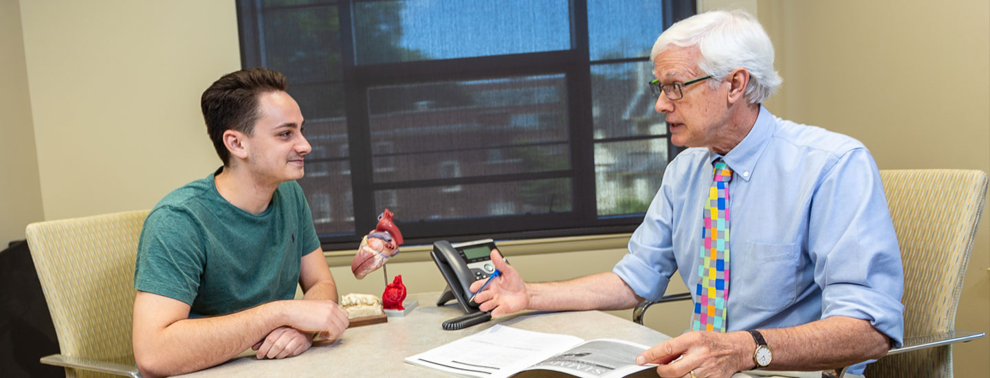 An undergraduate student meets with a science adviser to discuss the premedical-medical curriculum.
