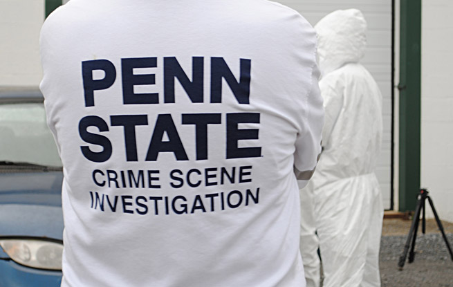 A forensics researcher in the field wearing a shirt that reads Penn State crime scene investigation.