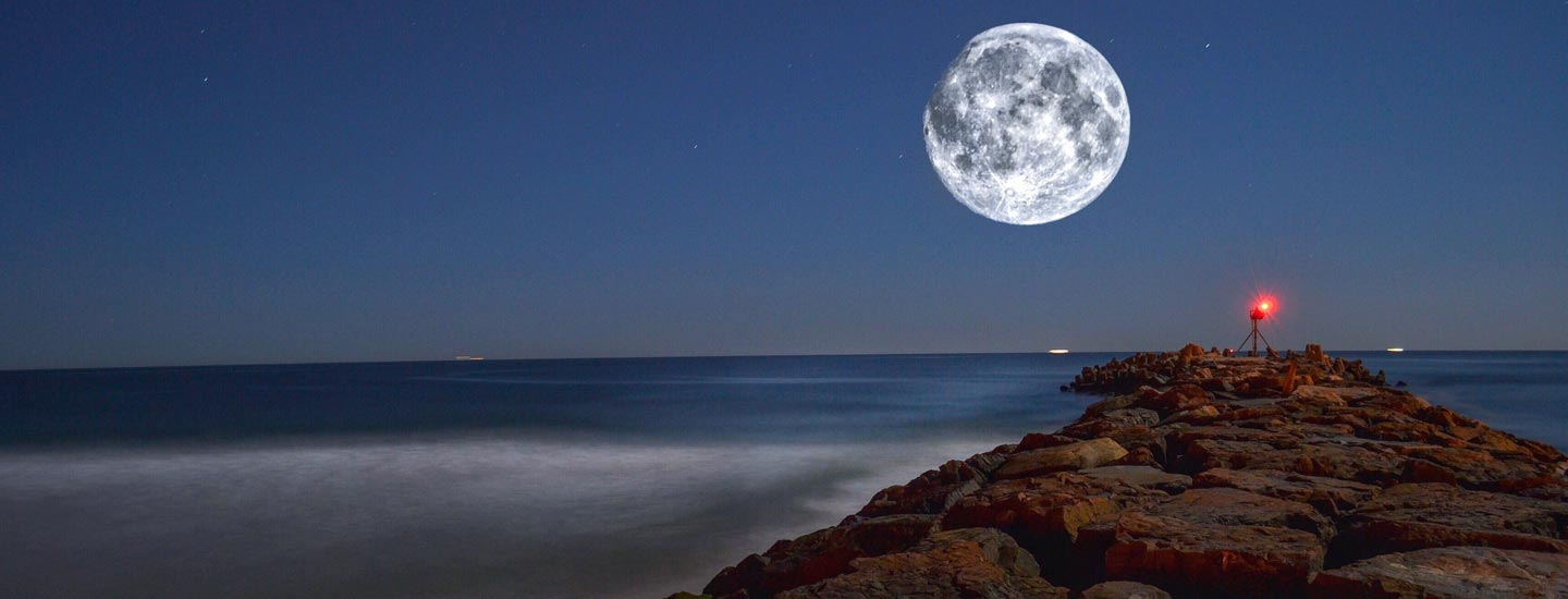 Composite image of a gibbous moon at 96 percent illumination, resting over the Atlantic Ocean.