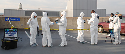 Forensic students process a mock crime scene on the East Parking Deck for CSI lab