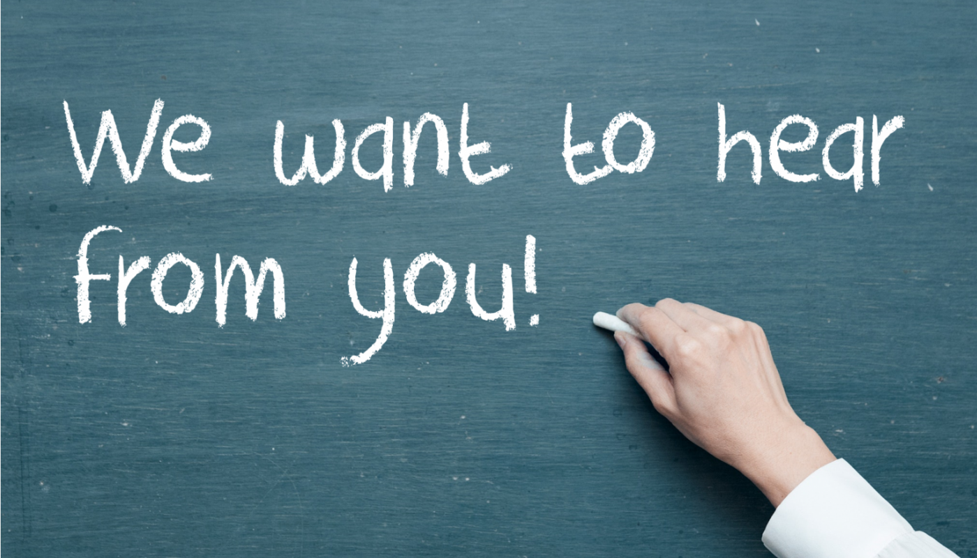 "Image of a hand writing on a chalkboard ""We want to hear from you""."