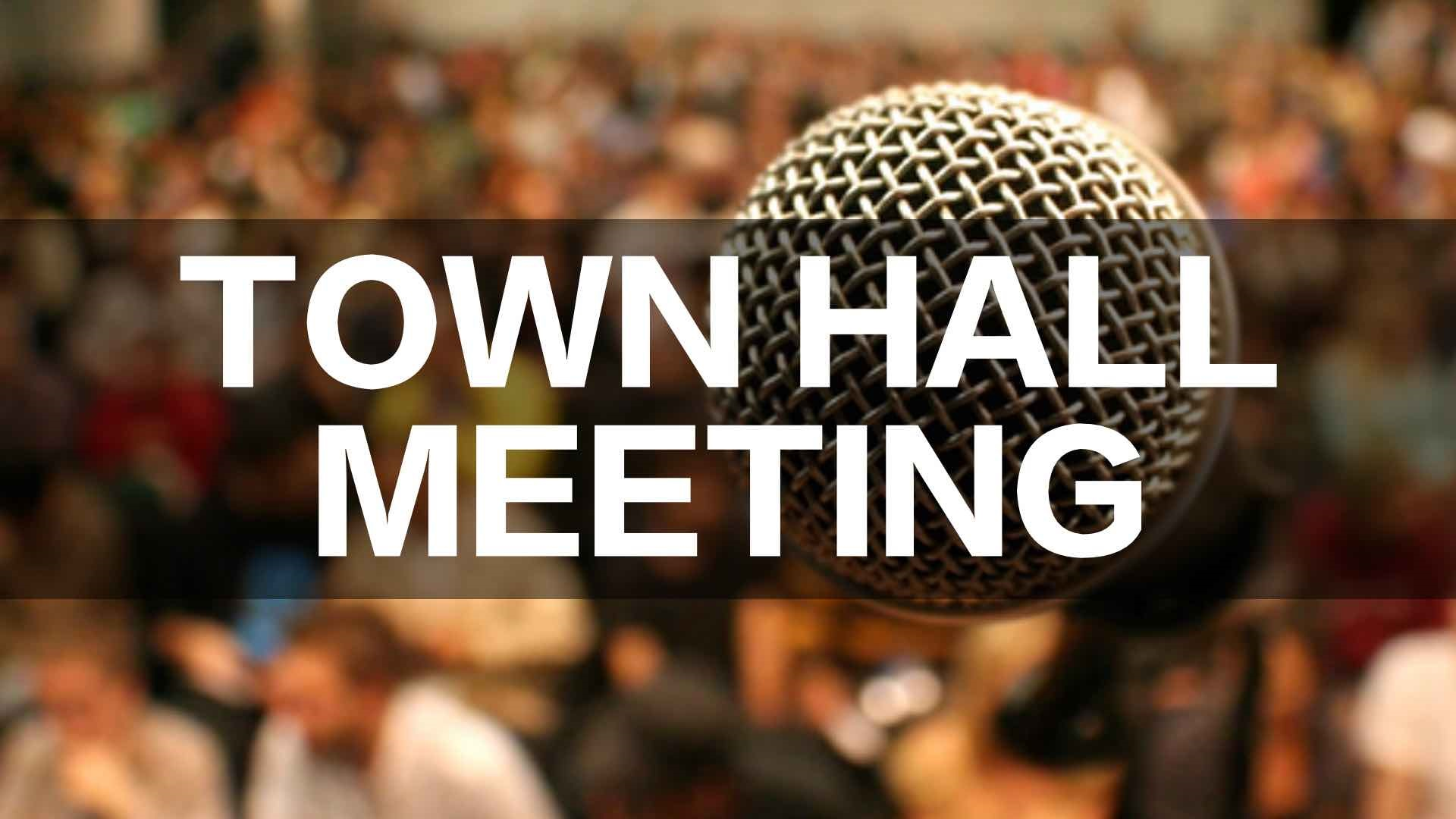 An image of a microphone in focus with blurred individuals in the background.  Text says Town Hall Meeting.