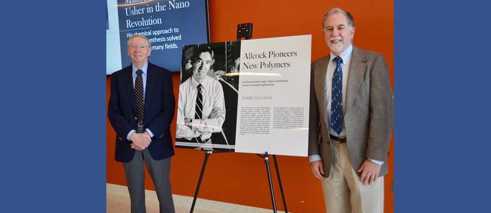 Harry Allcock (left) and Thomas Mallouk pose with a new poster about Allcock's pioneering research that will be permanently exhibited in the Millennium Science Complex. Credit: Maria Landschoot