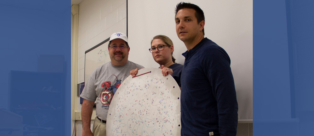 Teachers Keith Saroka, Valerie Knaver, and Lenny Barsody show a Sloan Digital Sky Survey plug plate. It is a surplus aluminum plate from the Apache Point Observatory that was used to help gather spectra from a specific set of astronomical objects.
