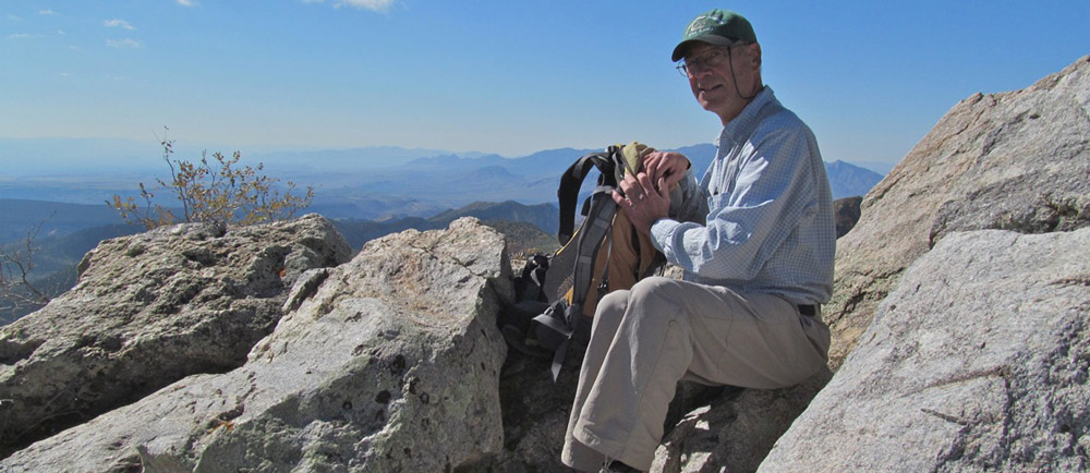 Alumnus Stephen Brumbach takes in the view at the summit of Mt. Bangs in the Paiute Wilderness Area in Arizona.