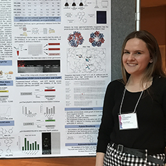 Image of Anna Brogan standing next to her research poster at the Undergraduate Research Exhibition at Penn State