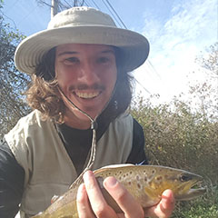 Image of Mac Meyer holding up a trout that he recently caught while fly fishing