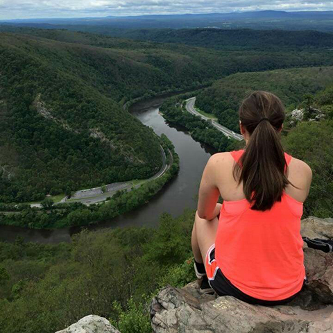 Image of Samantha Hartmann overlooking a beautiful river cutting through the mountains