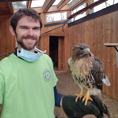 Image of TJ Russell holding a Red-Tail Hawk