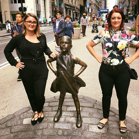 "Image of Holly Kleinschmidt and her mom standing in front of the ""Fearless girl"" statue in New York City"
