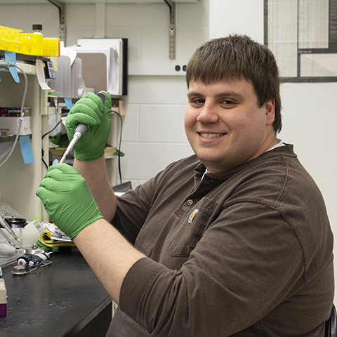 Image of Jacob Potter at the lab bench pipetting solution into a test tube