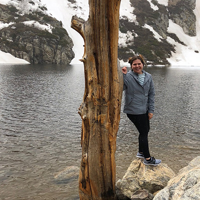Image of Kelly Rios standing next to a tree and by a lake