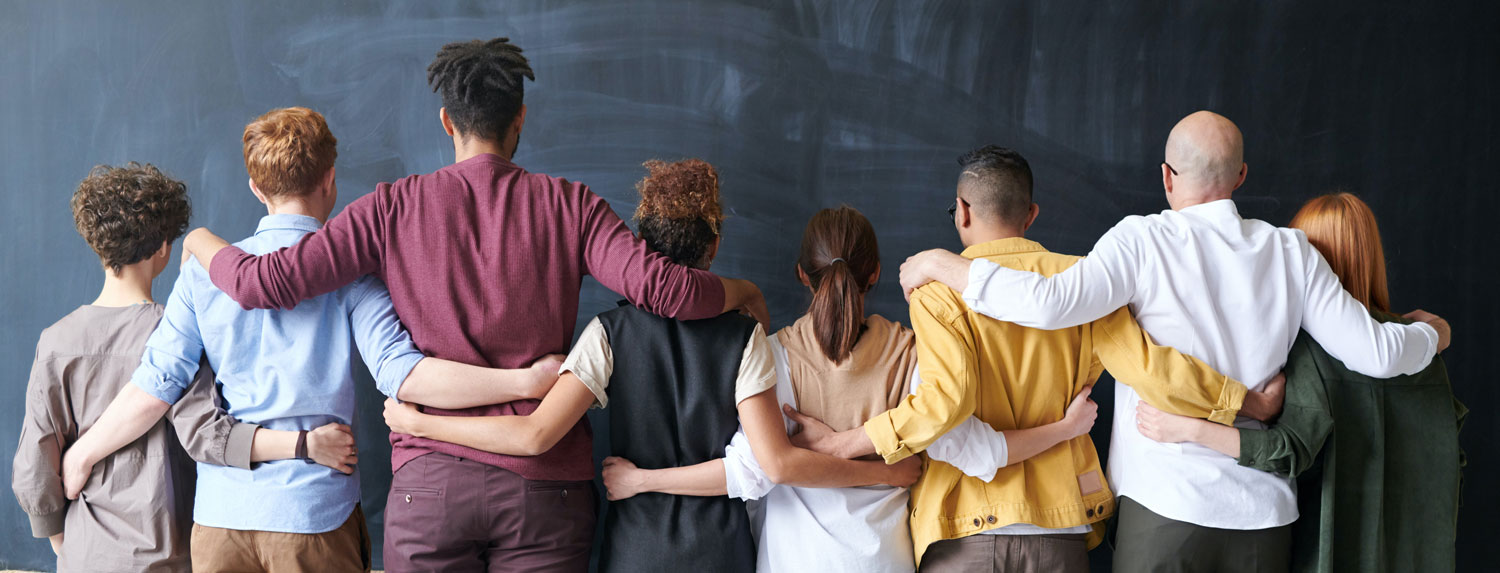 diverse people arm in arm looking at chalkboard