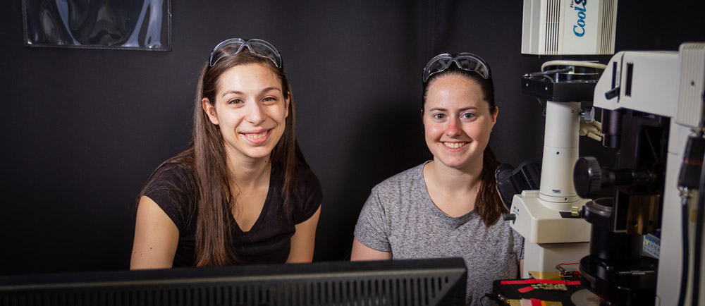 Two female students take a break from research to pose for the camera.