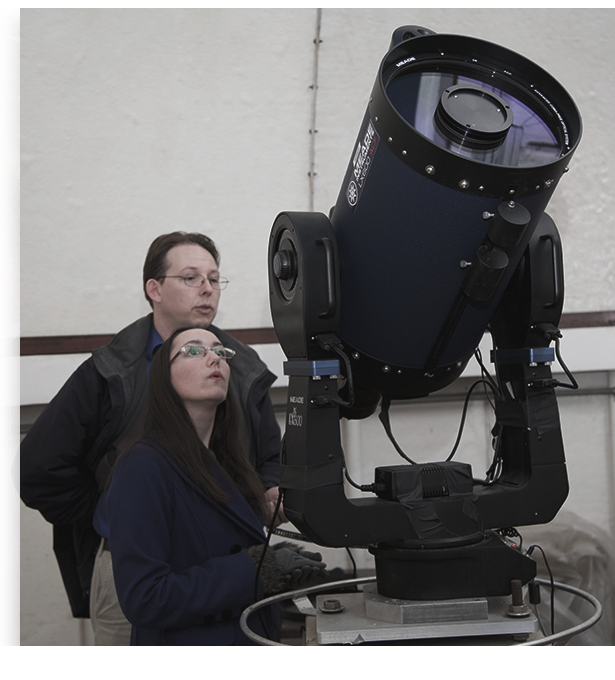 Female astronomer using telescope as male astronomer looks on