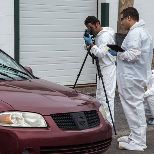 Researchers using a camera to document a mock crime scene involving ballistics and a car.