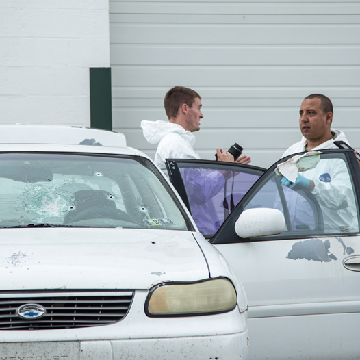 Researchers from Forensic Science analyzing bullet holes in a car at a mock crime scene.