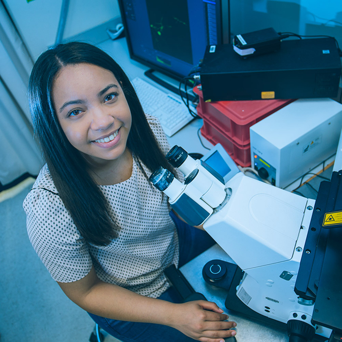 Karina Grullon at a microscope