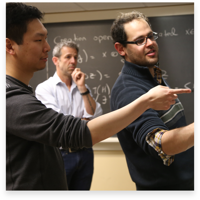 professors and students working a problem on the chalkboard