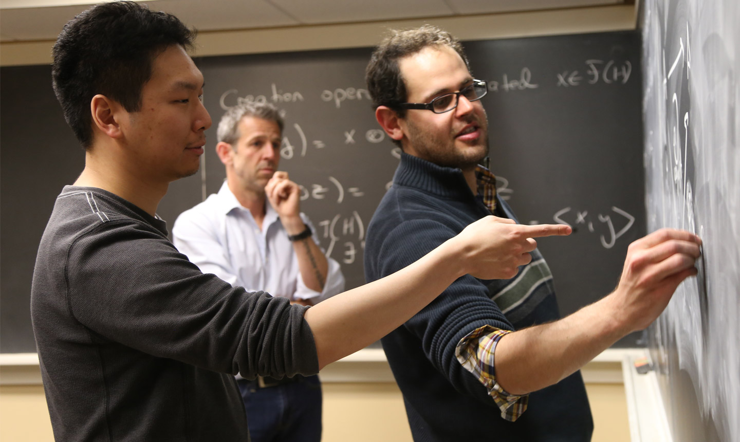 Two students and a professor work on equations on a chalkboard.