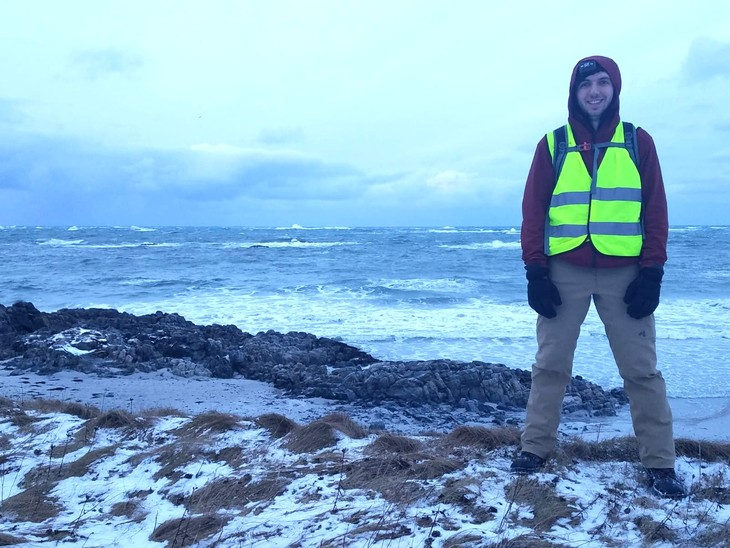 Penn State student Joshua Norfolk standing above the beach beside the Andøya Space Center.