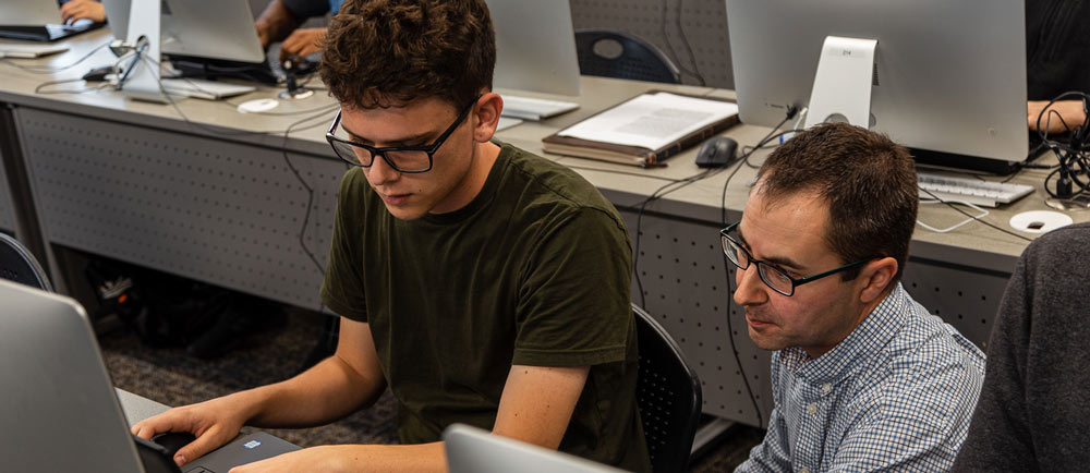 Students annotate genes collected by earlier CURE cohorts. Here Greg Broussard (right) works with a first-year student to properly annotate a phage sequence.