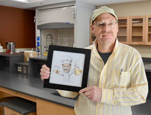 Joe Keiser holding a drawing of himself