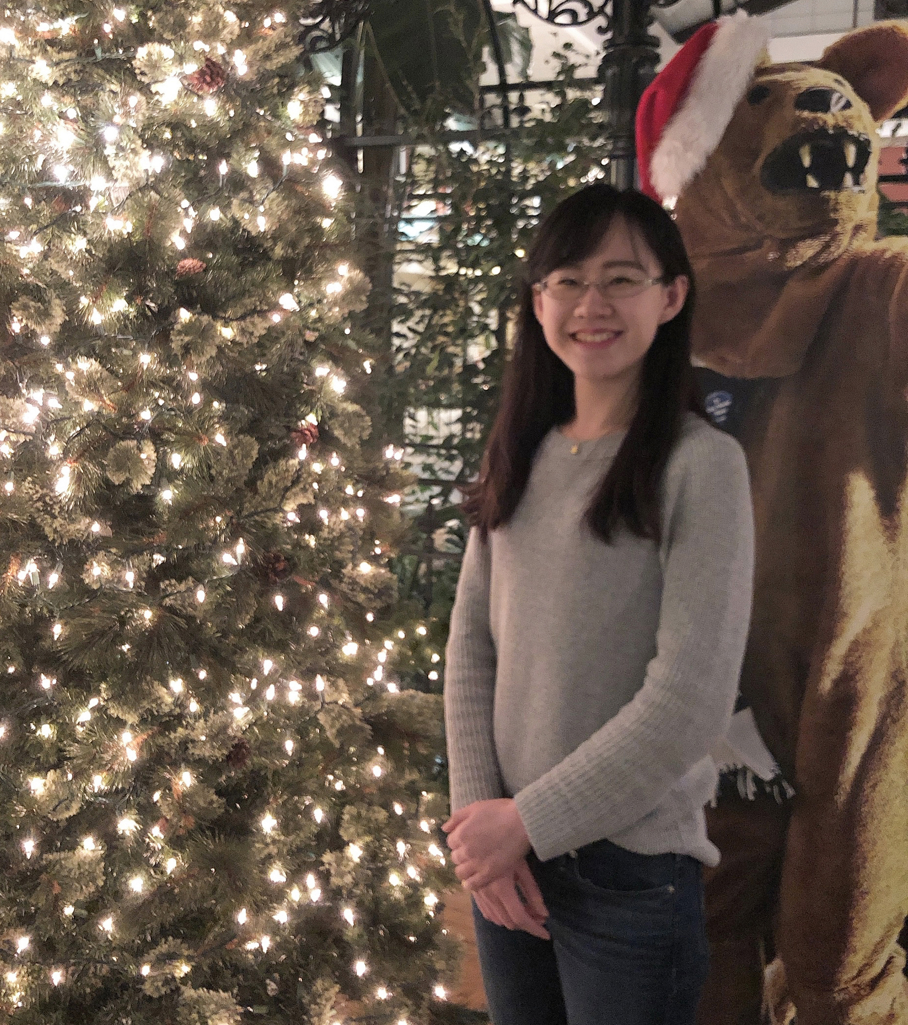 Xiaoran Xin posing in front of a light tree during the holidays