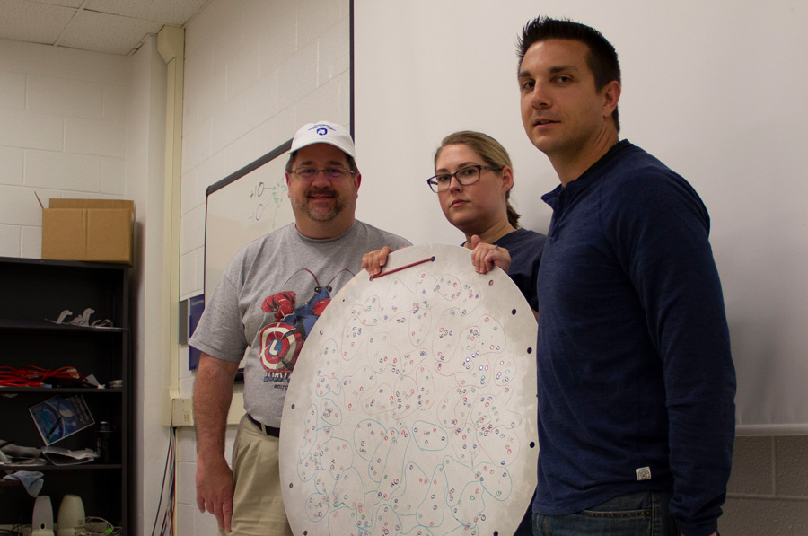 Teachers Keith Saroka, Valerie Knaver, and Lenny Barsody show a Sloan Digital Sky Survey plug plate. It is a surplus aluminum plate from the Apache Point Observatory that was used to help gather spectra from a specific set of astronomical objects. Most plates are recycled, but some go to teachers to use as a tool in their classroom for teaching some astronomical methods.