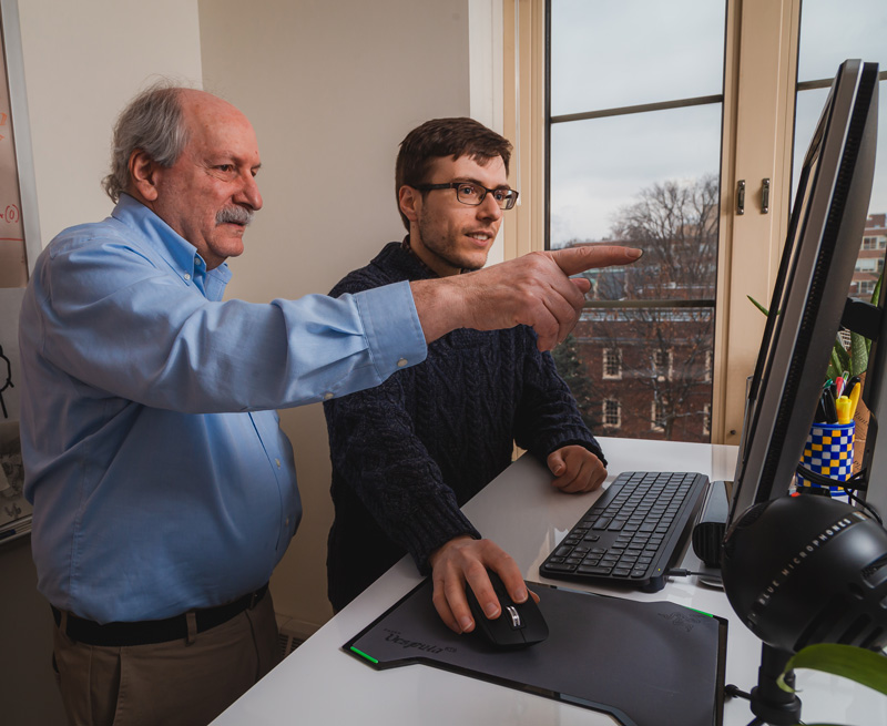Dennis Pearl (left) and Bob Carey discuss the software students use to create statistics-related songs through SMILES. Credit: Nate Follmer.