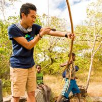 Joaquim Diego Santos learning how to shoot a primative bow and arrow from local tribe children
