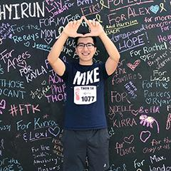 Image of Yashar Yaxiaer in front of a signature wall for Penn State's Dance Marathon
