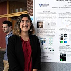 Image of Anjali McNeil standing next to her undergraduate research exhibition poster