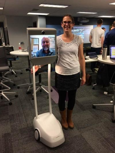 a woman with a robot with a man video calling in