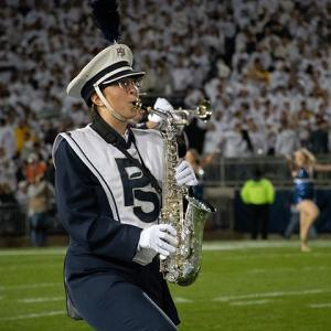 Image of Cassidy Prince marching on the field with her saxophone as part of the Penn State Blue Band