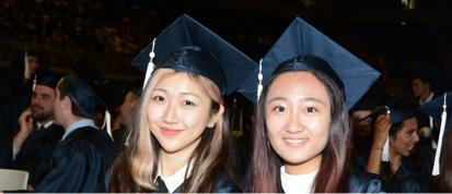 Two female students in graduation caps.