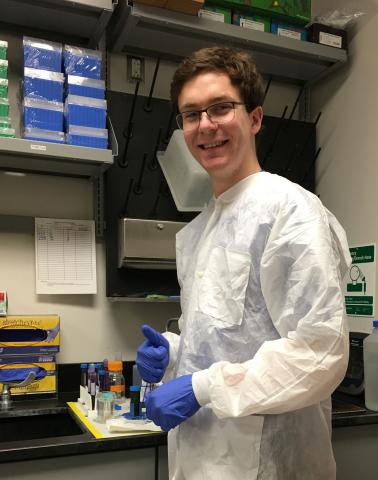 Cuyler Luck in lab coat and gloves